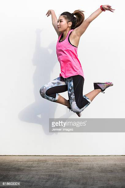 Sporty Asian woman doing aerobic jump in front of white wall.