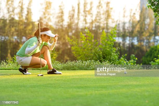sporty asian woman golf player crouching and study the green before putting shot in vacation and holiday.  sport and healthy concept - 女子 ゴルフ ストックフォトと画像