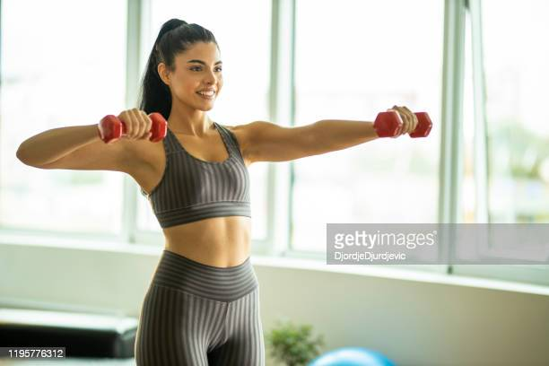 sporty beautiful woman exercising at home to stay fit - dumbbell stock pictures, royalty-free photos & images