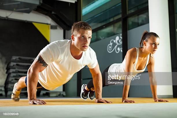 Casal desportivo exercício no ginásio fitness
