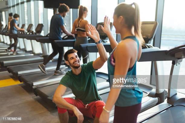 couples sportifs donnant le haut cinq l'un à l'autre à la gymnastique - salle de gym photos et images de collection