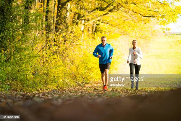 sporty couple running together in forest - mature couple stock pictures, royalty-free photos & images