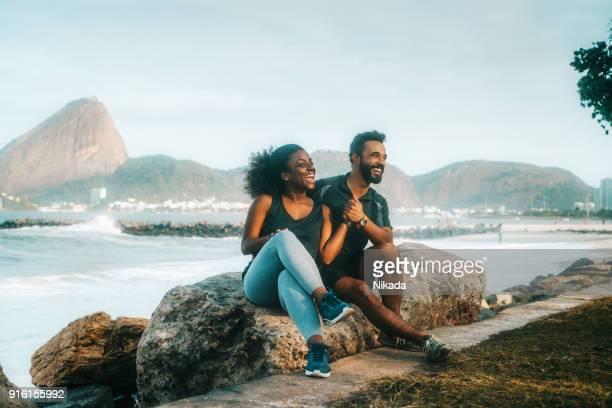 desportivo casal sentado na praia rocha - rio de janeiro - fotografias e filmes do acervo