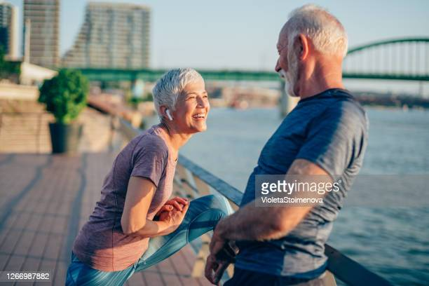 sporty couple stretching outdoors - warming up stock pictures, royalty-free photos & images