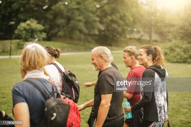 sporty female and male senior friends walking in park - 70 79 jaar stockfoto's en -beelden