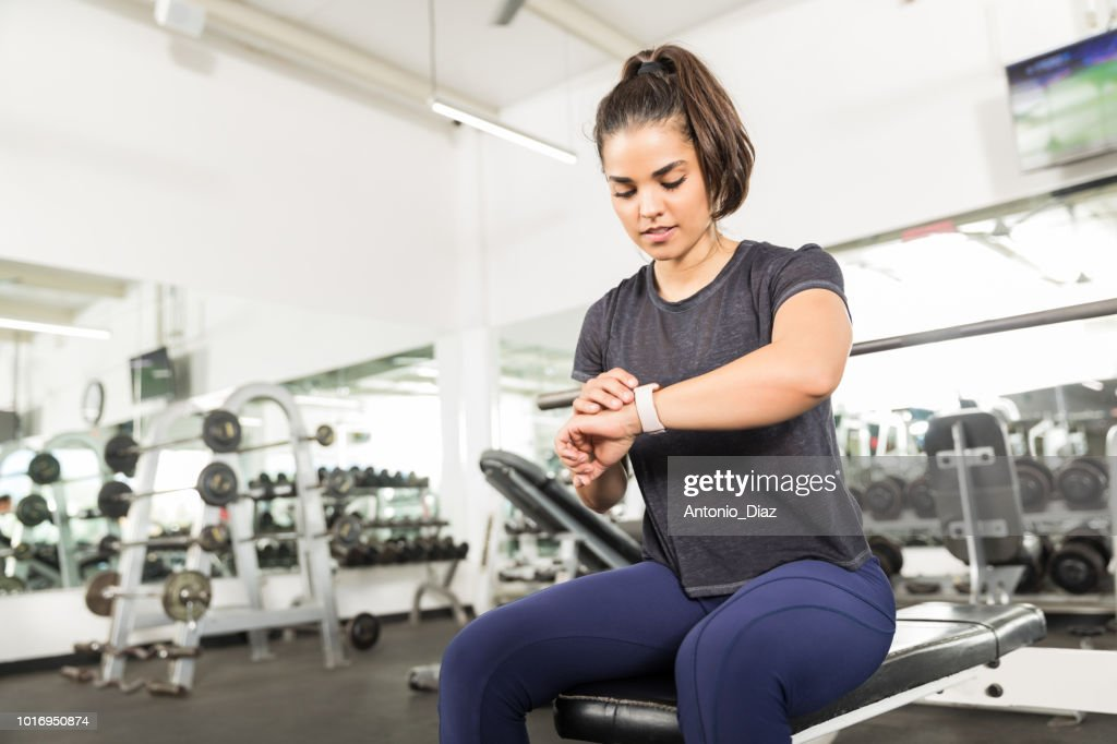 Sporty Female Checking Fitness Activity On Smart Watch In Gym : Stock Photo