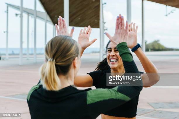 sporty friends giving a high-five after workout together. - effort stock pictures, royalty-free photos & images