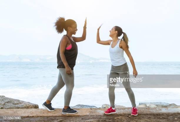 sportliche Freunde geben High-Five am Strand im sonnigen Tag