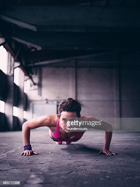 Sporty girl doing push ups and looking determined