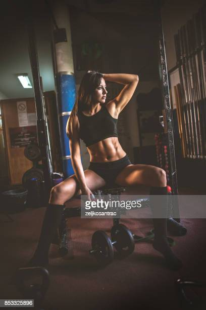 Sporty girl lifting weights in gym