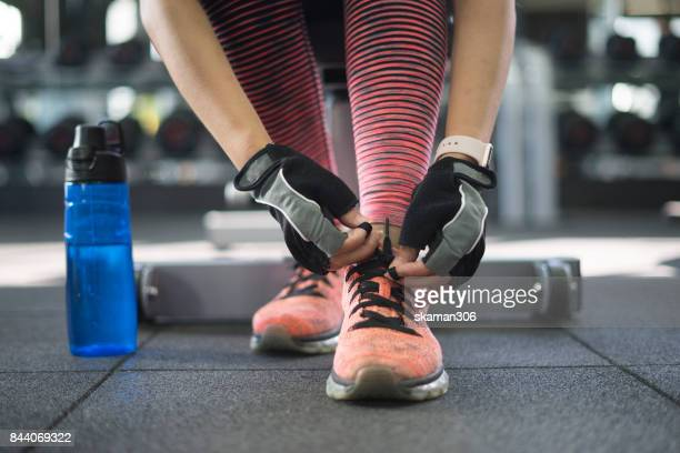 sporty girl work out at gym and fix the rope of sport shoe with water bottle and wearing glove