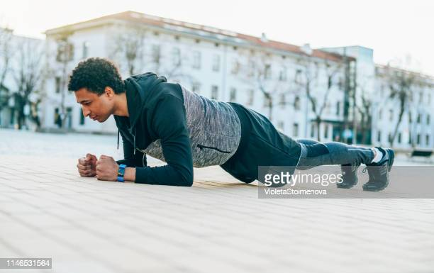 sporty man doing plank - plank exercise stock pictures, royalty-free photos & images