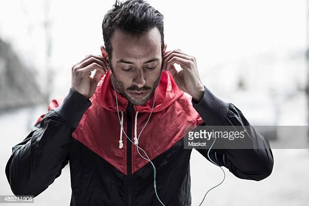 Sporty man in jacket adjusting headphones