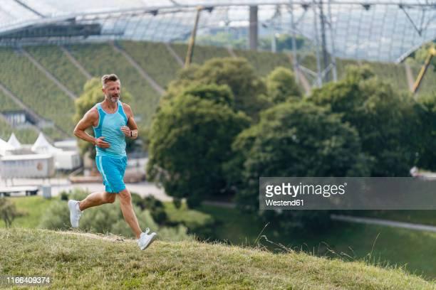 sporty man jogging in a park - olympischer park veranstaltungsort stock-fotos und bilder