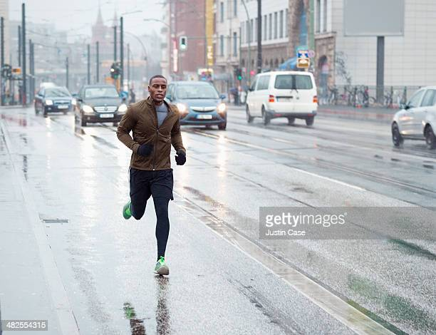 sporty man jogging through rainy city scape