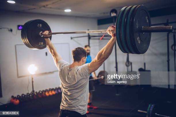sporty man lifting weights - barbell stock pictures, royalty-free photos & images
