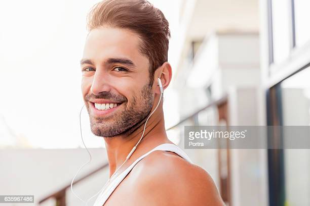 Sporty man listening music though headphones