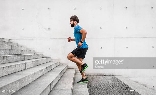 sporty man running up steps in urban setting - sportkleidung stock-fotos und bilder