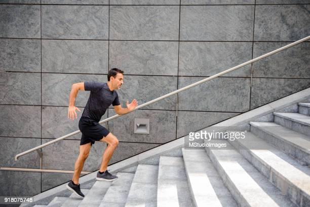 階段を走っているスポーティな男