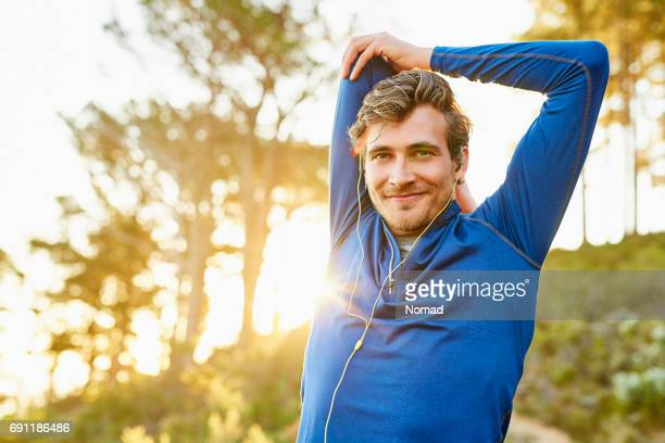 Sporty man stretching arm and shoulder outdoors