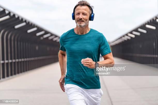 sporty man wearing headphones and jogging - joggen stock-fotos und bilder