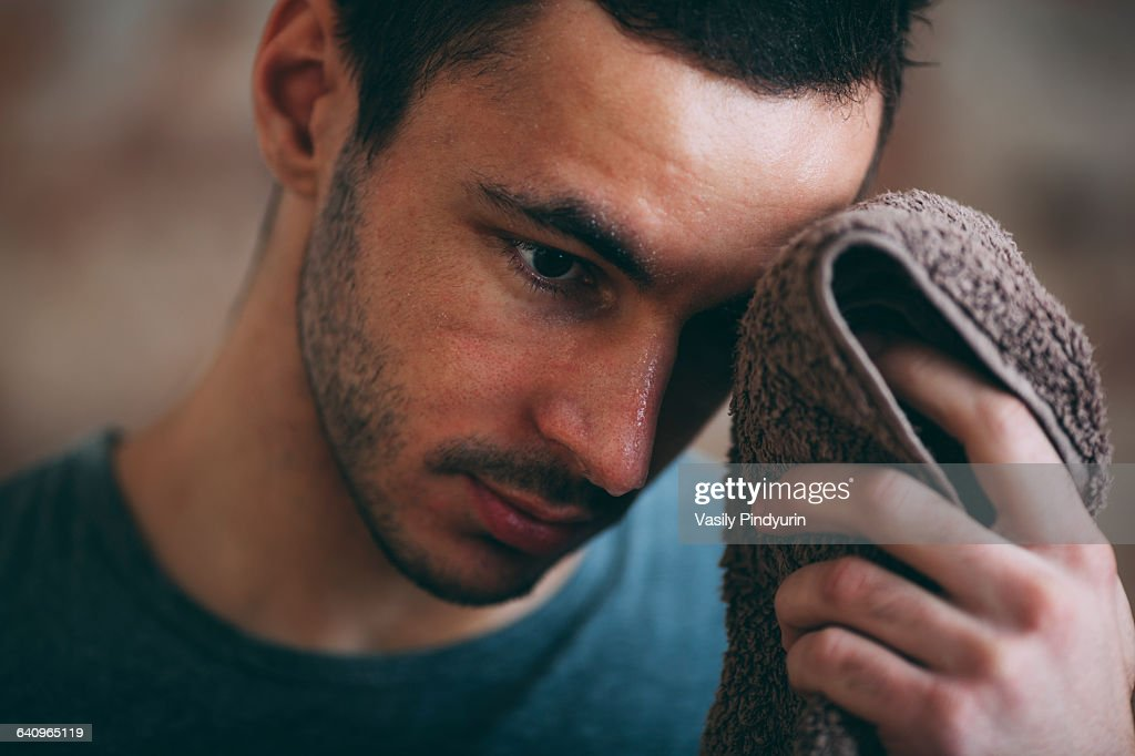 Sporty man wiping sweat on forehead at gym : Stock Photo