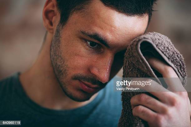 sporty man wiping sweat on forehead at gym - rubbing stock pictures, royalty-free photos & images