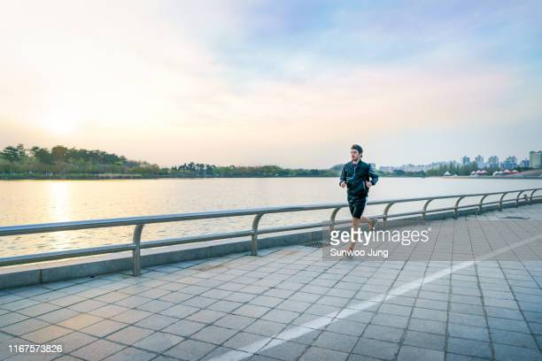 sporty man with earphones jogging at lake park - ランニングショートパンツ ストックフォトと画像