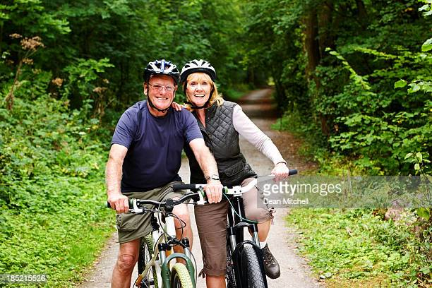 Sporty mature couple with bicycle in countryside