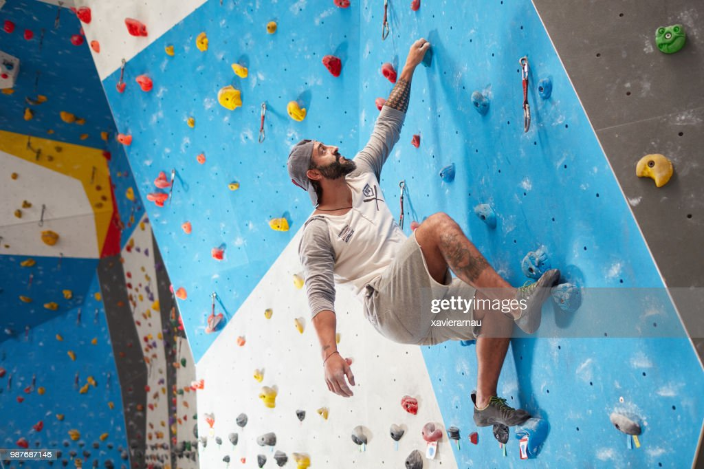 Sporty mature man climbing wall in gym : Stock Photo