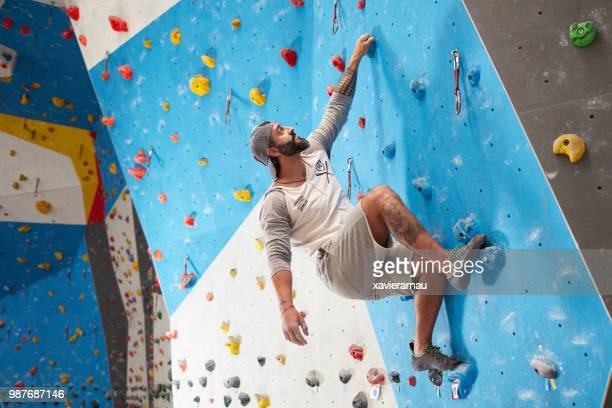 Sporty mature man climbing wall in gym