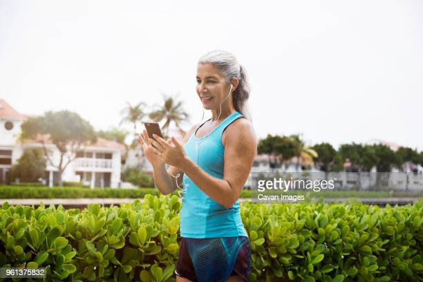 sporty mature woman listening music through smart phone against clear sky - aventura florida stock photos and pictures