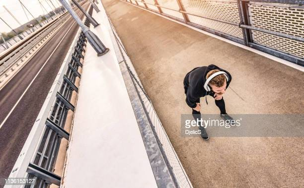 sporty mid adult man resting on a bridge after a sprint. - leaning stock pictures, royalty-free photos & images