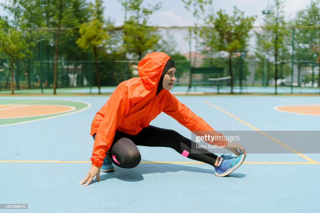 sporty muslim woman and runner with hijab stretching legs in the park : Stock-Foto