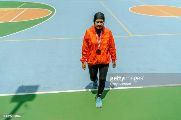 sporty muslim woman and runner with hijab walking in a park