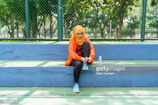 sporty muslim woman with glasses fixing shoes in a sport park