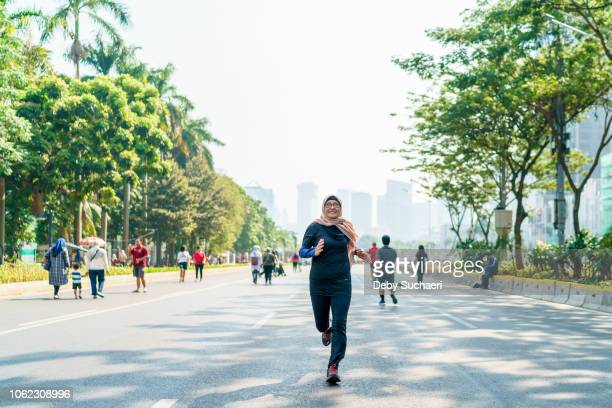 sporty muslim woman with hijab running on the big street frontal