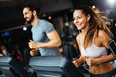 Sporty people running on treadmills in a health club