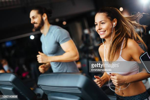 sporty people running on treadmills in a health club - gym stock pictures, royalty-free photos & images