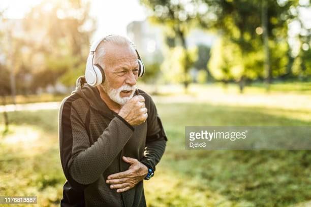 sporty senior man coughing. - cough stock pictures, royalty-free photos & images