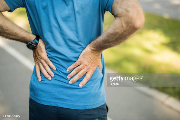 sporty senior man having a back pain close up. - backache stock pictures, royalty-free photos & images