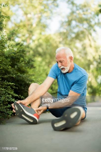 sporty senior man having a leg injury. - old man feet stock pictures, royalty-free photos & images
