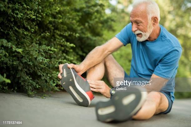 sporty senior man having leg injury outdoors. - old man feet stock pictures, royalty-free photos & images