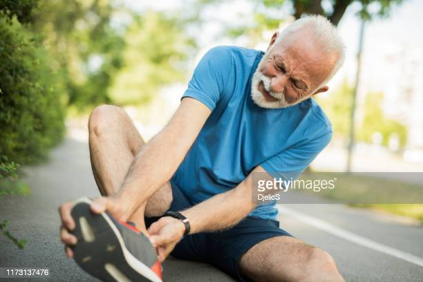sporty senior man having leg injury outdoors. - foot stock pictures, royalty-free photos & images