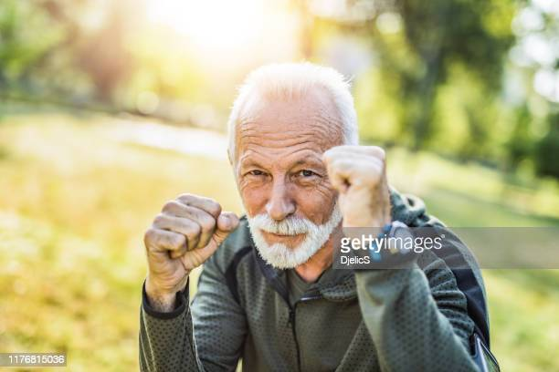 sporty senior man loves boxing and is stronger than ever. - combat sport stock pictures, royalty-free photos & images
