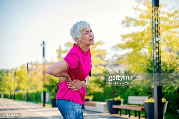 sporty senior woman having a back pain. woman getting injured while training outdoors. athletic woman having backpain - herniated disc stock pictures, royalty-free photos & images