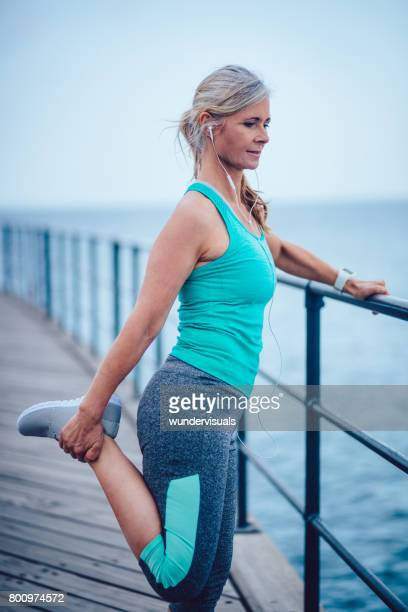 sporty senior woman stretching her legs getting ready for running - older woman legs stock photos and pictures