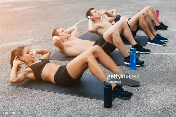 sporty team of two women and two men, situps - 自重トレーニング ストックフォトと画像