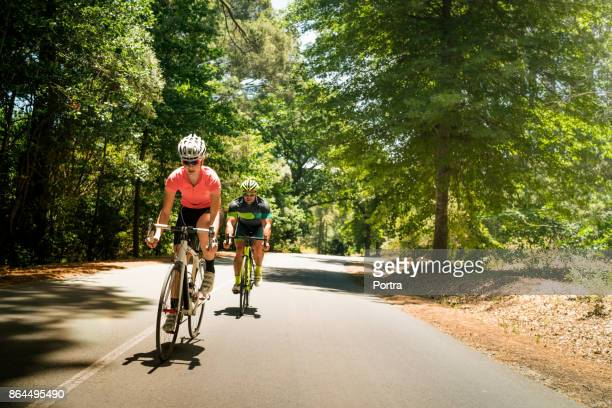 Sporty woman and man riding bicycles on road