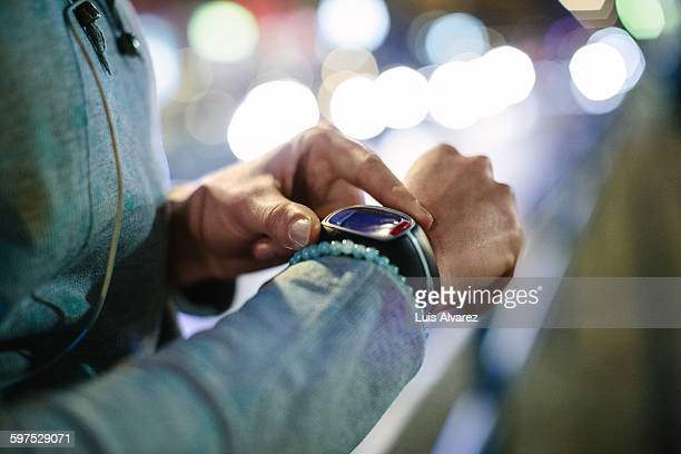 sporty woman checking time on smart watch - ver a hora - fotografias e filmes do acervo